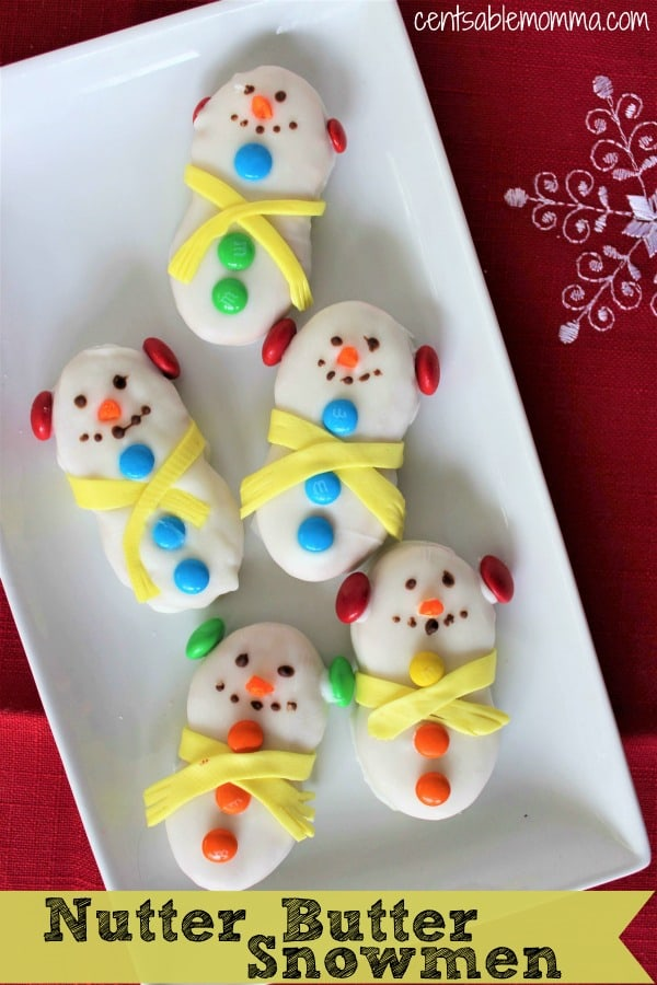 This super cute Nutter Butter Snowmen recipe is perfect for your holiday party or a great craft to do with the kids to make their own snack. All you need is Nutter Butter cookies, some white melting chocolate, and some candy (like M&M's, Laffy Taffy, and candy corn) to get started.