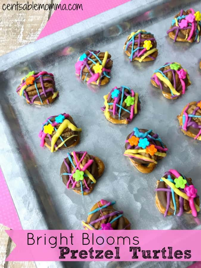 Easily create these fun Bright Blooms Pretzel Turtles for spring. They're a delicious mix of both savory and sweet and are created with pretzels, Rolo candies, pecans, colored chocolate, and daisy sprinkles. Super cute!